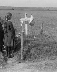 Copiii unui soldat mort pe front ii aduc un omagiu in mormantului sapat in locul in care a cazut. A fost cazul multor soldati, de peste tot, ingopati de camarazii lor.