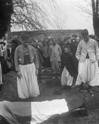 combatanti algerieni ingopand, infasurat in steagul frantei, pe unul din camarazii lor