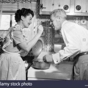 1950-femme-au-foyer-dans-la-cuisine-apres-avoir-mari-gouter-la-nourriture-sur-cuisiniere-cmr82y