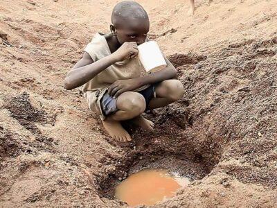 Copil somalez care bea apa murdara